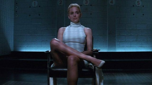 Sharon Stone sitting alone in a chair with her legs crossed