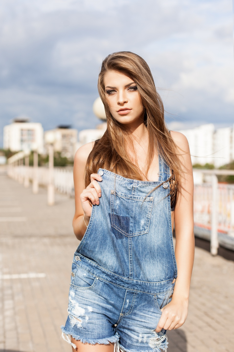 Beautiful girl with long silky hair in denim short overalls