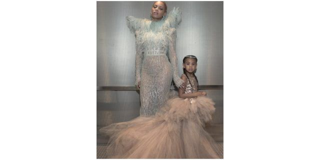 Beyoncé and her daughter, Blue Ivy, dressed in pale pink and white couture, stand together.