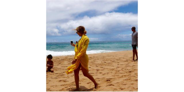 Blue Ivy sits on the sand as Jay Z walks behind her, and Beyoncé takes a photo of her daughter on the beach.