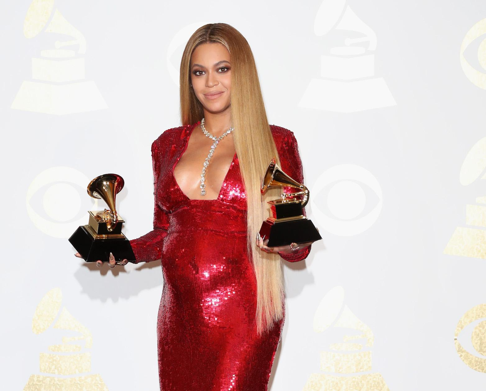 Beyoncé smiles as she holds two Grammy Awards while wearing a sequined red maternity gown.