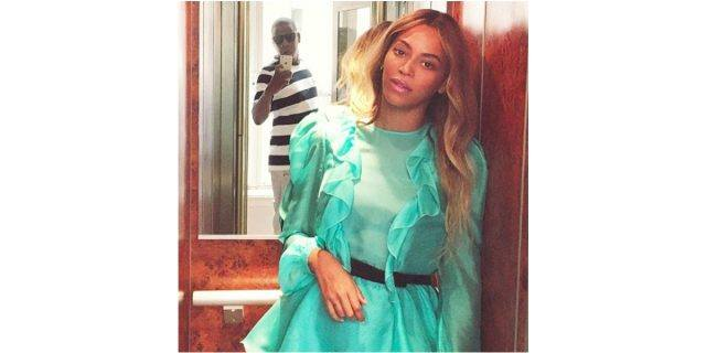 Jay Z takes a photo of Beyoncé, and his reflection is visible in the mirror behind her.