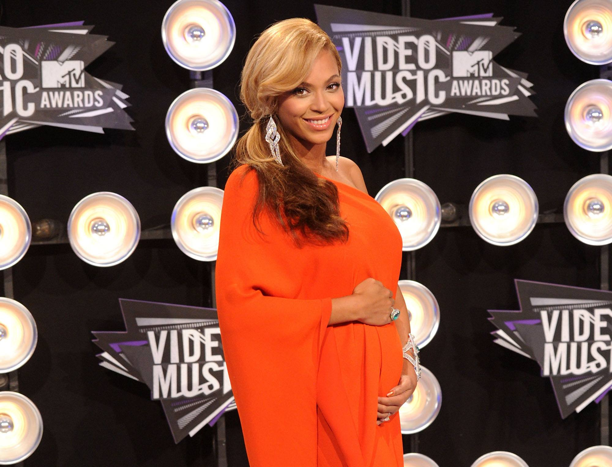 Beyoncé arrives at the 2011 MTV Music Video Awards wearing an orange asymmetrical gown.
