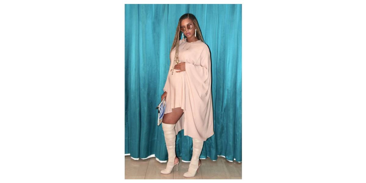 Beyoncé wears a cream-colored dress and stiletto boots as she poses holding her baby belly in an Instagram photo.