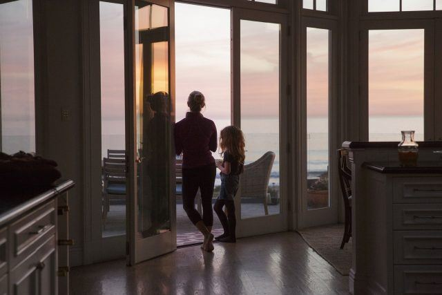 Madeline and Chloe stand in the doorwall leading out to their patio and watch as the sun goes down in a scene from 'Big Little Lies.'