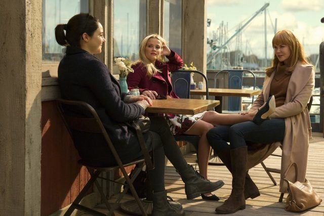 Jane sits at an outdoor coffee shop table with Madeline and Celeste while Madeline props her leg up on Celeste's lap in a scene from 'Big Little Lies.'