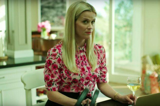 Madeline holds a glass of wine as she sits in front of her computer in the kitchen in a scene from HBO's 'Big Little Lies.'