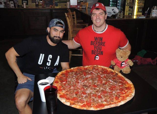 two men with huge pizza