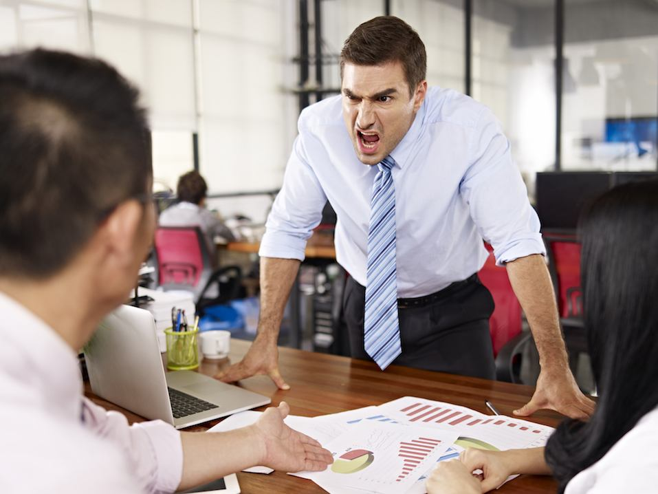 caucasian business executive yelling at two asian subordinates in office.