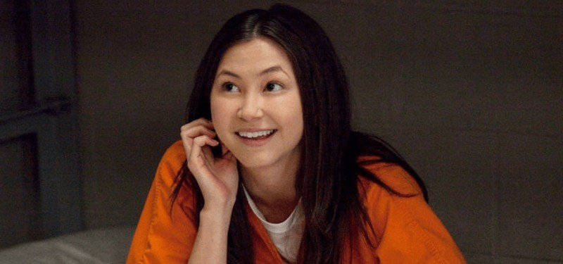 In a scene from Orange Is the New Black, Brook Soso is in an orange jumpsuit and is smiling.