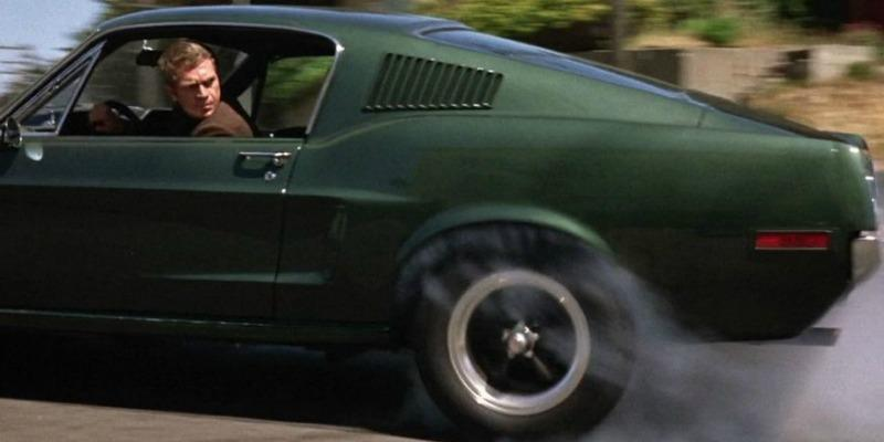 Steve McQueen is speeding away in a mustang and looking back out of the window.