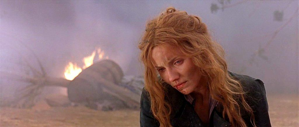 Cameron Diaz as Jenny Everdeane looking down sadly in front of ruins and fire in Gangs of New York