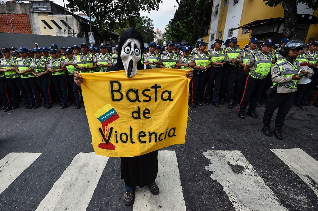 """A person holds a banner reading """"Enough of Violence"""" at a 2016 protest in Caracas, one of the most violent cities."""