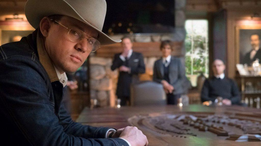 Channing Tatum wearing a cowboy hat while sitting at a table, turning to look into the camera