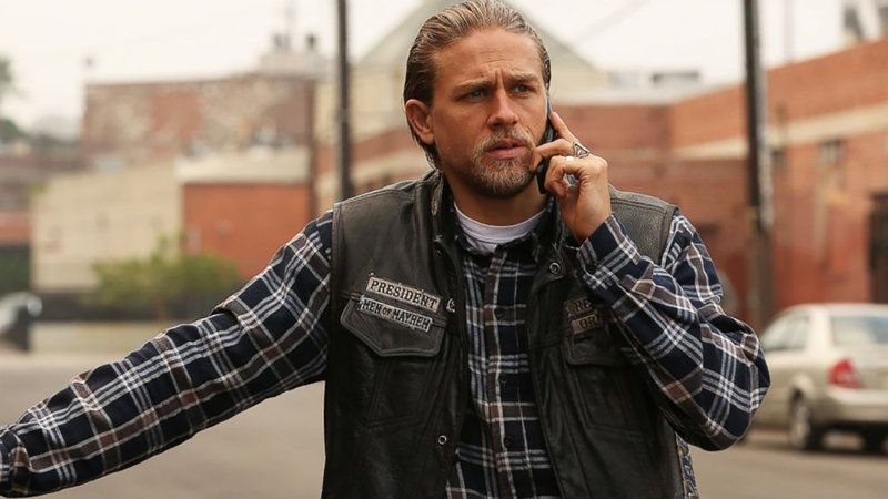 """Charlie Hunnam as Jax in a plaid shirt and vest that says """"President"""" talking on a cell phone on Sons of Anarchy"""