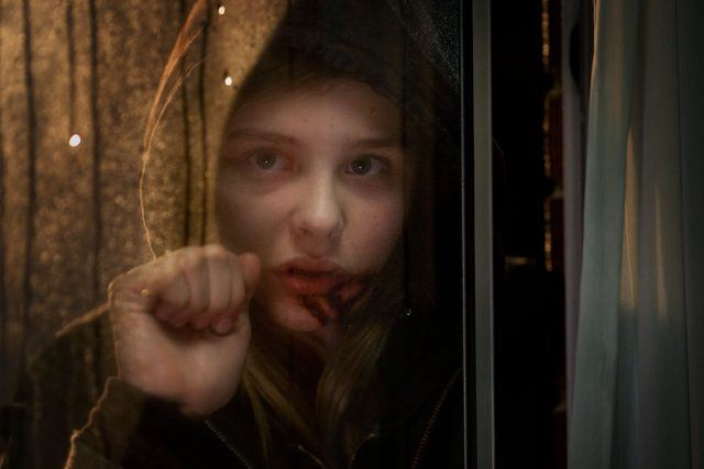 Abby wears a hood and knocks on a window in a scene from 'Let Me In.'