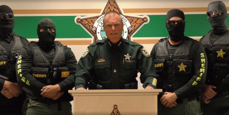 Police officers speak at a podium