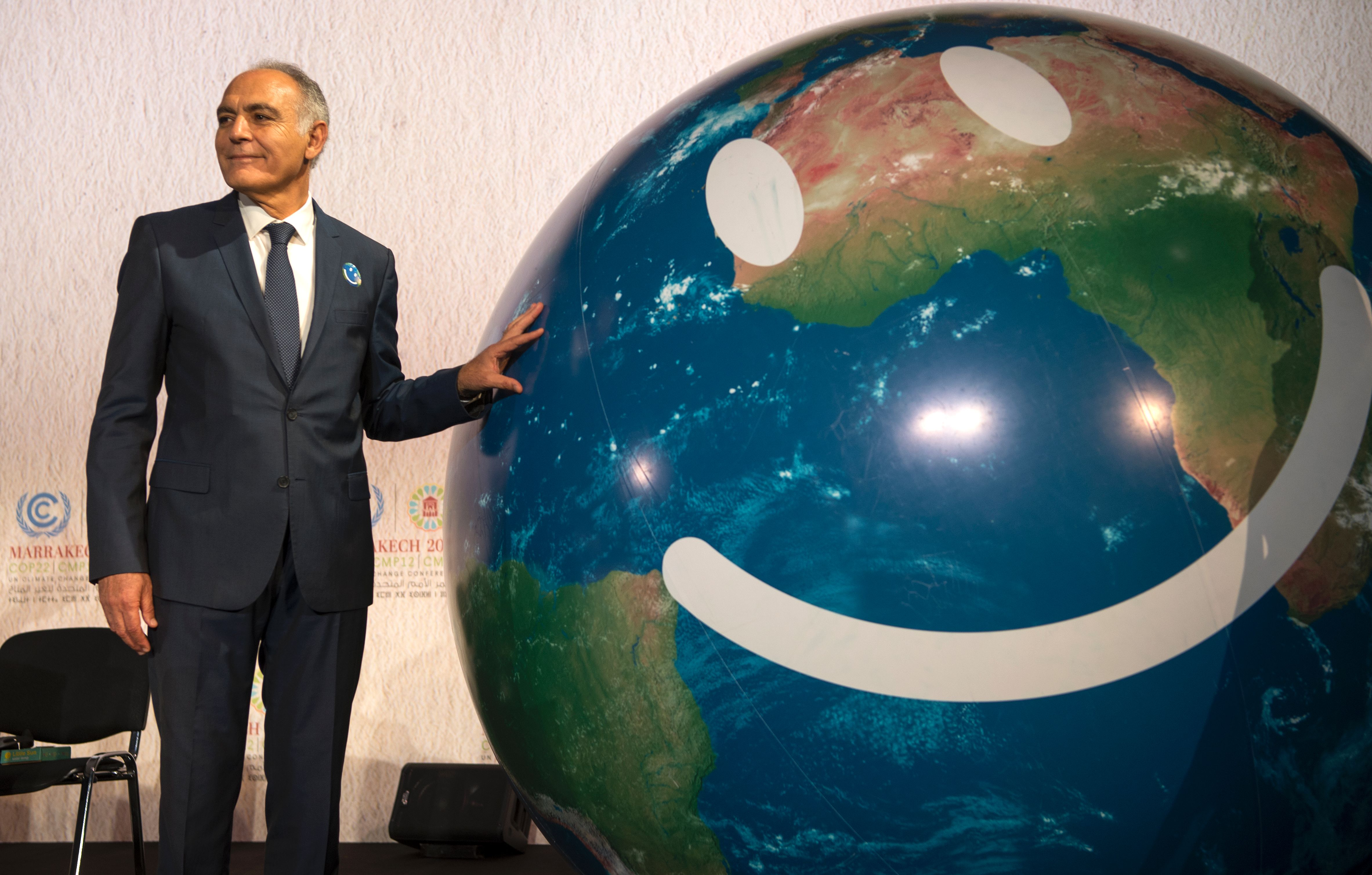 COP22 president Salaheddine Mezouar caresses a smiley Earth ball during a climate change summit