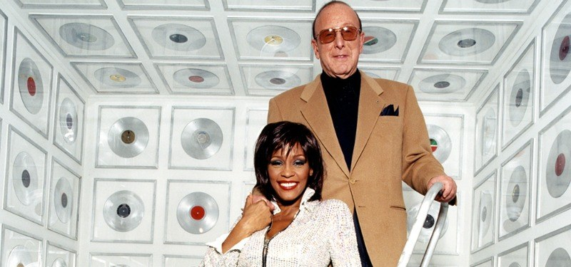 Clive Davis and Whitney Houston stand in a room full of records.