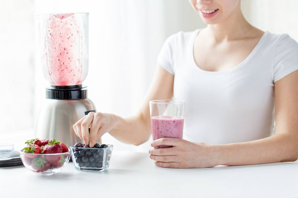 woman with blender, smoothie, and berries