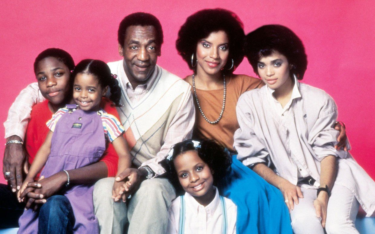 The cast of the The Cosby Show poses together in front of a pink background