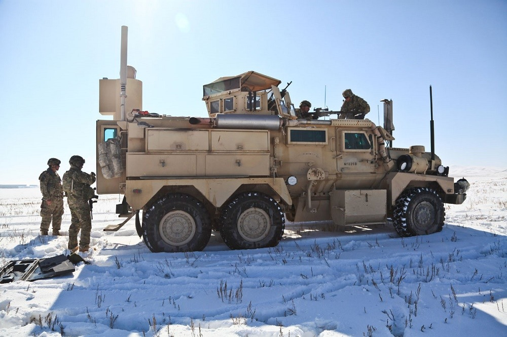 Soldiers stand outside a Cougar 6x6 MRAP in a snowy field.