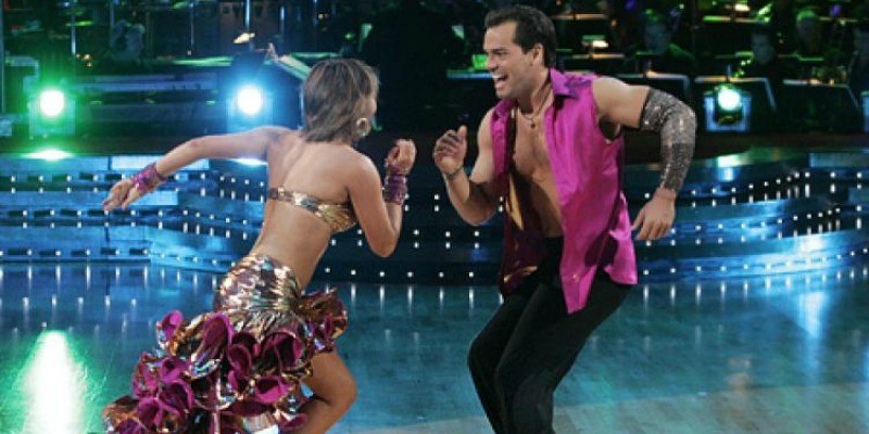 Cristian de La Fuente and Cheryl Burke are looking at each other while dancing.