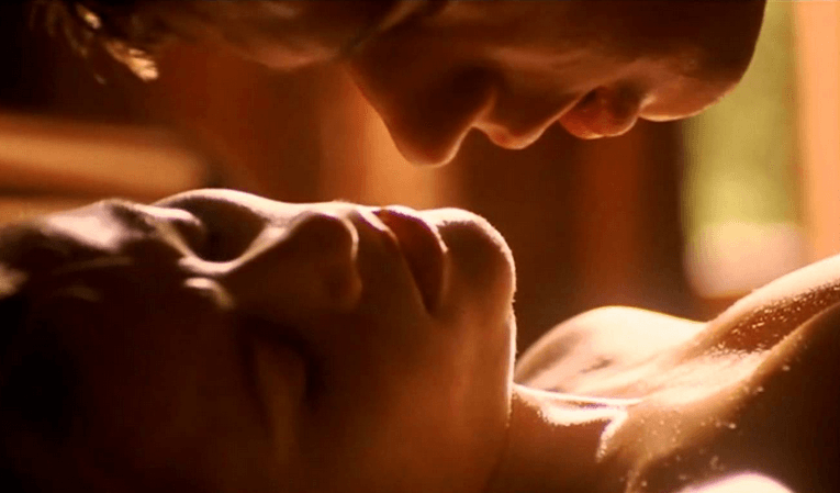 A close-up on Reese Witherspoon and Ryan Phillippe in bed together, naked
