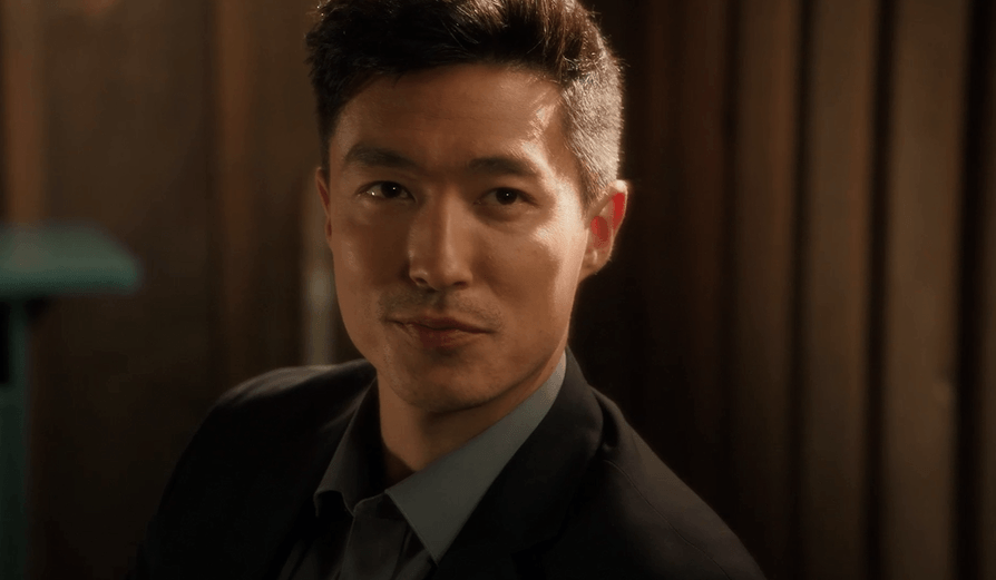Daniel Henney, wearing a suit and smiling
