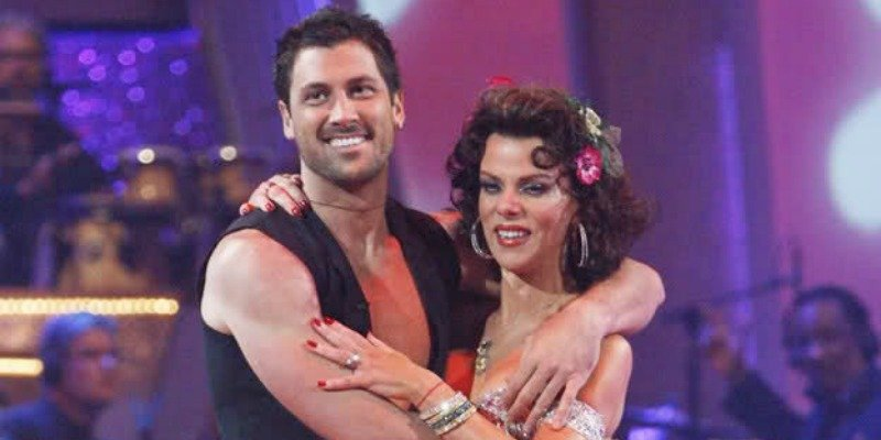 Debi Mazar and Maksim Chmerkovskiy have their arms around each other while listening to the judges.
