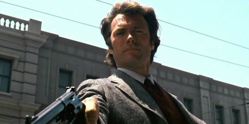 Clint Eastwood as Harry is pointing a gun downward.
