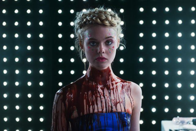 Jesse (Elle Fanning) stands looking at the camera, her face decorated with jewels, and blood covering her neck and chest, in 'Neon Demon.'