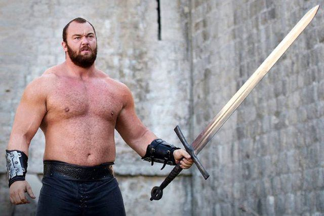 The Mountain, a.k.a. Gregor Clegane, stands, shirtless, and brandishes a long sword in a scene from 'Game of Thrones.'