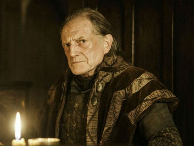 Walder Frey sits at a table, a lit candle in front of him, in a scene from 'Game of Thrones.'