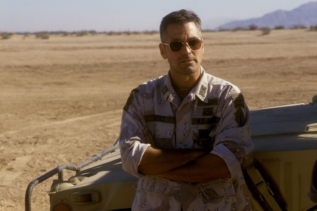 George Clooney wearing army fatigues, leaning against a jeep