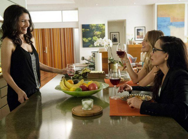 Linda Edelstein, Beau Garrett and Janeane Garofalo sit around a kitchen counter, drinking wine and talking, in a scene from 'Girlfriends' Guide to Divorce.'