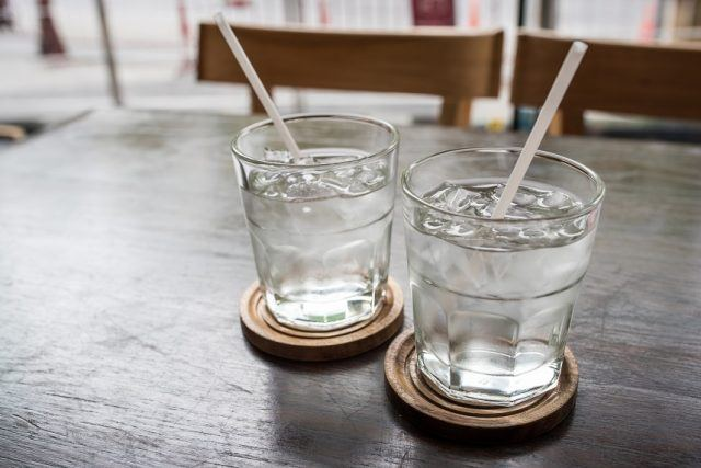 Two glasses of water on a dark wooden table.