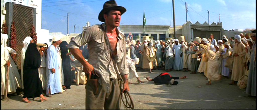 Harrison Ford holstering his gun in Raiders of the Lost Ark with a whip in his left hand