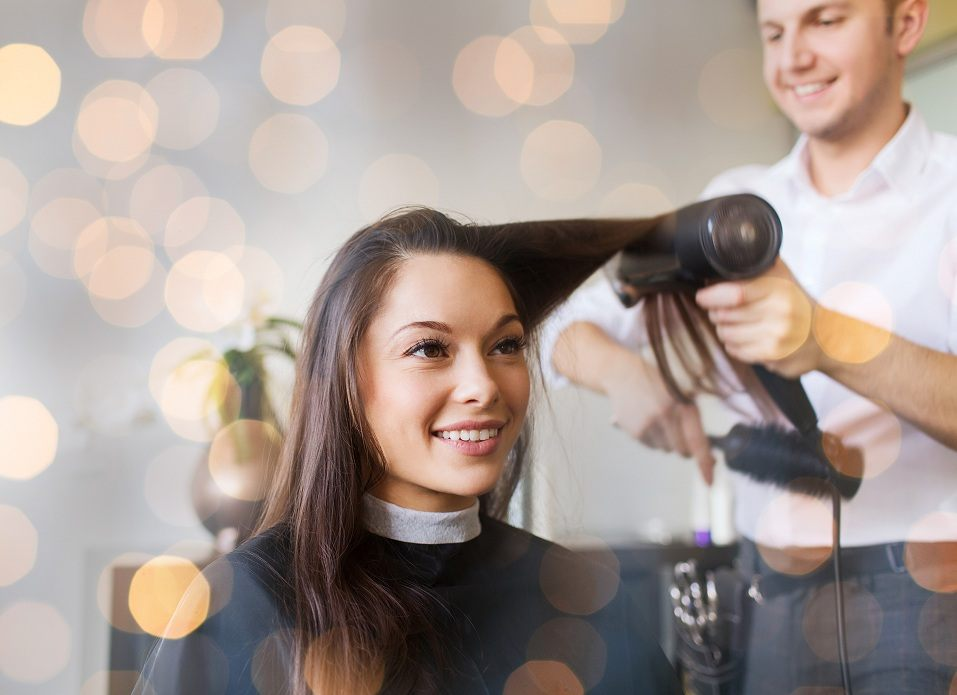 happy young woman and hairdresser with fan