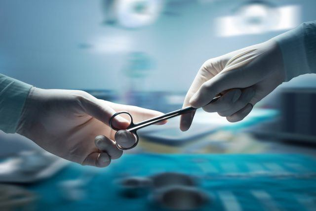 Close-up of surgeons hands holding surgical scissors and passing surgical equipment , motion blur background.