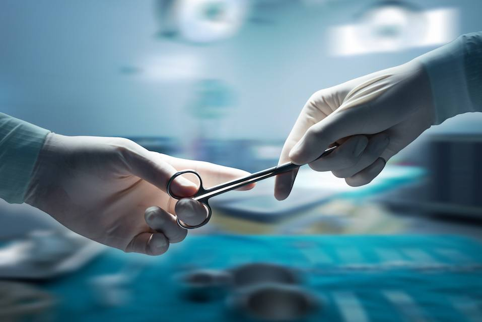 Close-up of surgeons hands holding surgical scissors