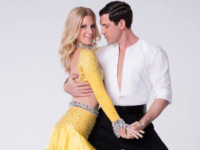 Heather Morris wears a sparkly yellow two piece costume as she poses with her 'Dancing With the Stars' partner, Maksim Chmerkovskiy.