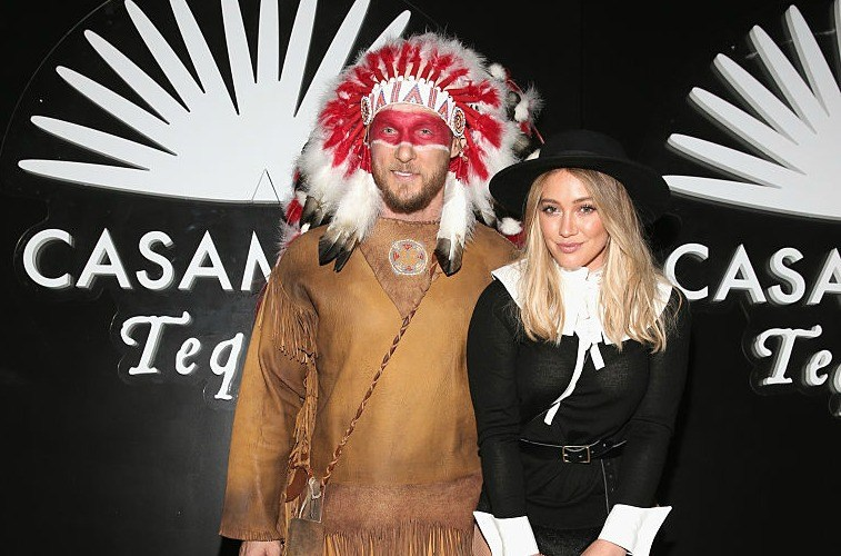 Trainer Jason Walsh in a Native American costume standing with girlfriend Hilary Duff in a pilgrim costume in front of a back wall that reads 'Casamigos Tequila'