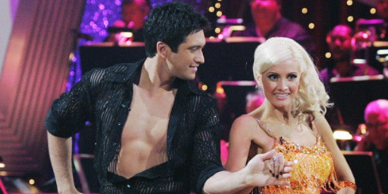 Dmitry Chaplin is holding Holly Madison's hand and is looking at her while dancing.