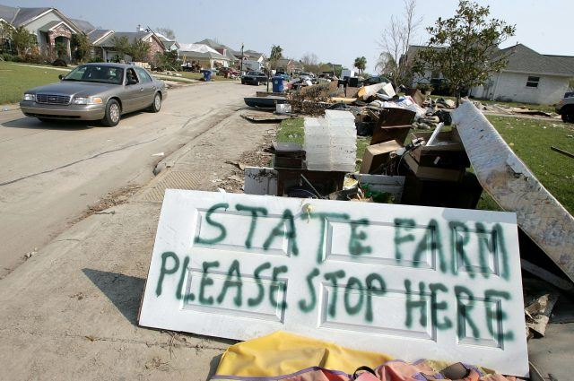 """sign that says """"state farm please stop here"""" on a damaged street"""