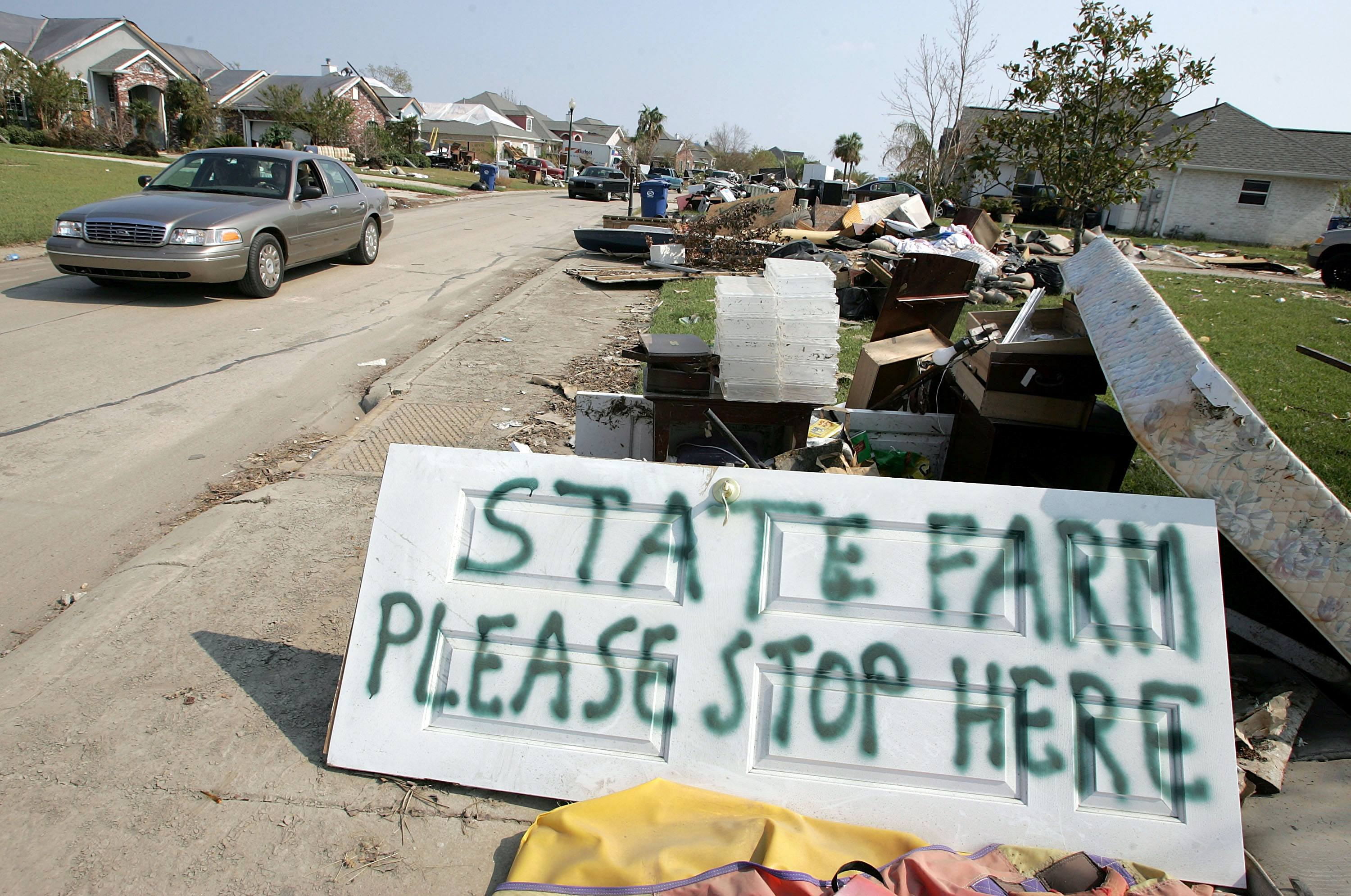 A sign in front of a damaged home asks for an insurance adjuster to stop