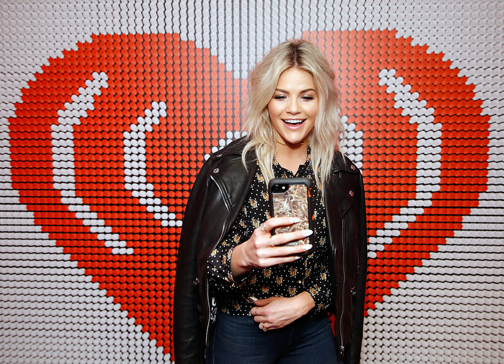Witney Carson poses with her phone