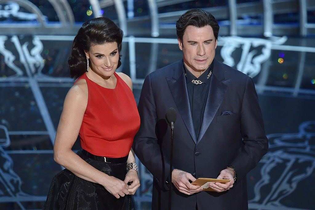 Actors Idina Menzel and John Travolta onstage in formalwear presenting at the Oscars as John holds an envelope