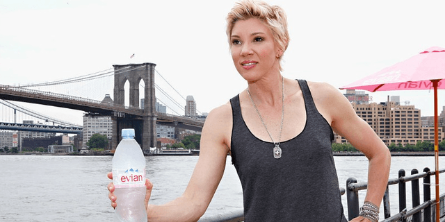 Jackie Warner holds an Evian bottle while posing in a tank top in front of a bridge and a river