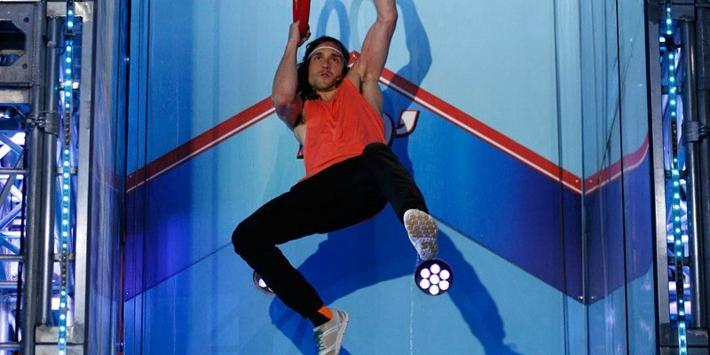 Jake Murray in a red tank top swinging from ring to ring while competing